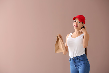 Young woman with paper bag on color background. Food delivery service Imagens - 114665186