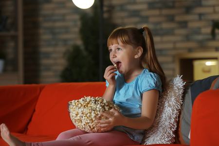Little girl eating popcorn while watching TV on sofa in evening Banco de Imagens