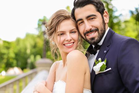 Gelukkige jonge bruid met haar bruidegom buitenshuis