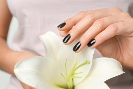 Woman with stylish black manicure holding lily flower, closeup