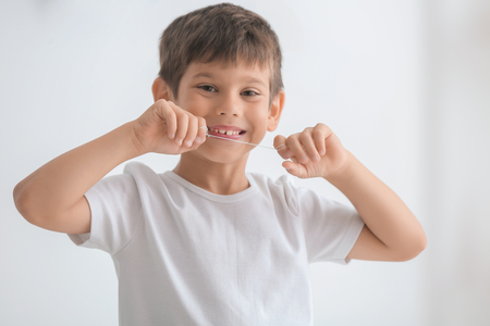 Cute little boy flossing his teeth on light background 免版税图像