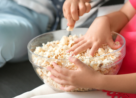 Little children eating popcorn while watching TV on sofa, closeup