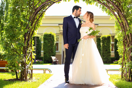 Happy wedding couple under floral arch outdoors