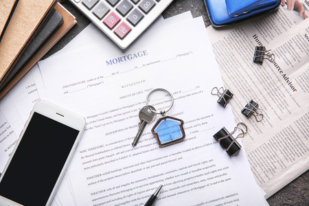 Key with trinket, phone and mortgage contract on table Stok Fotoğraf - 114668836