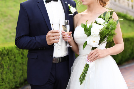 Happy wedding couple with glasses of champagne outdoors