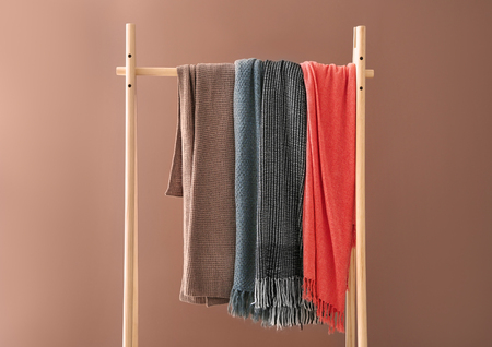 Wooden rack with warm plaids on color background