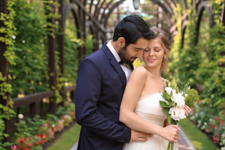 Happy newlyweds with beautiful wedding bouquet outdoors