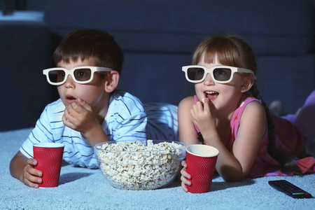 Cute children in 3d glasses watching movie on carpet in evening Foto de archivo