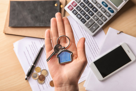 Woman holding key with trinket. Mortgage concept
