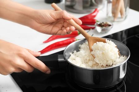 Woman with spoon stirring rice in saucepan, closeup