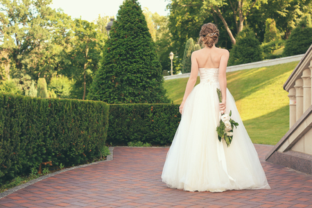 Beautiful young bride with wedding bouquet outdoors