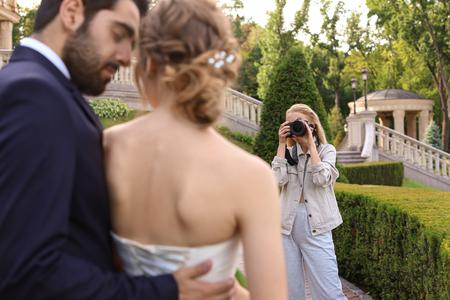 Professional photographer taking photo of wedding couple outdoors Stock fotó