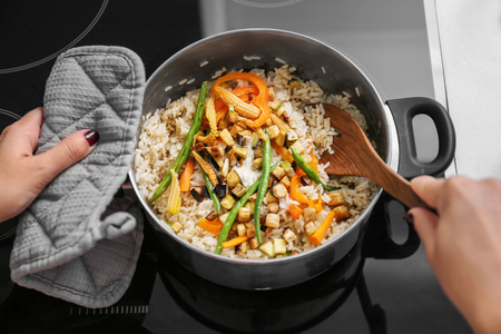 Woman cooking tasty rice with vegetables in kitchen Stock fotó