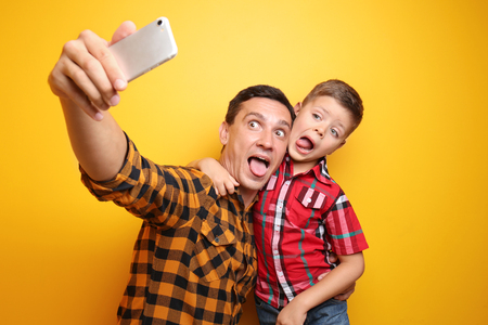 Little boy and his dad taking funny selfie on color background Stockfoto