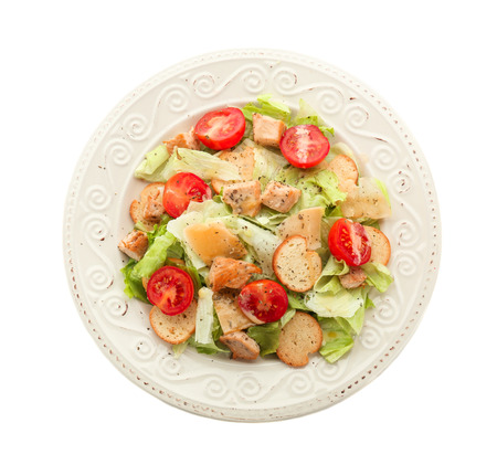 Plate with tasty Caesar salad on white background