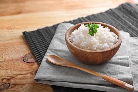 Schüssel mit gekochtem weißem Reis auf Holztisch