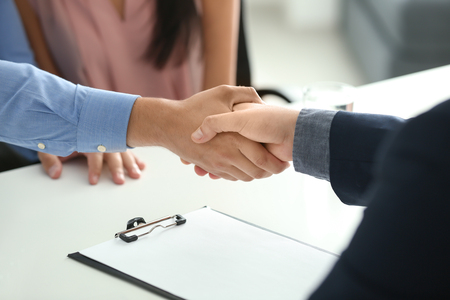 Young man shaking hands with estate agent in office