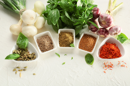 Composition with different spices on white textured background Фото со стока