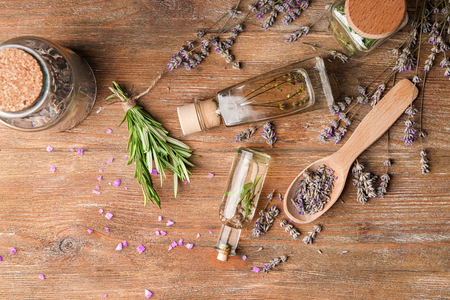Bottles of essential oil with lavender and rosemary on wooden table