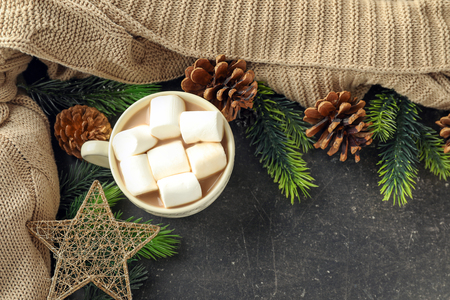 Cup of hot cocoa with marshmallows and Christmas decorations on table