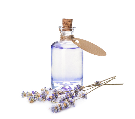 Bottle of essential oil with lavender on white background