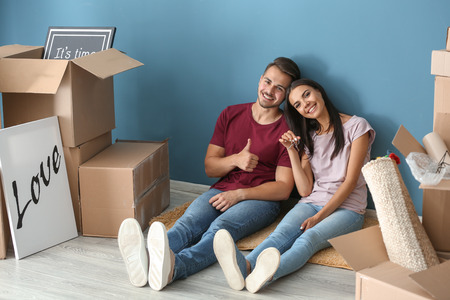 Young happy couple with key and moving boxes sitting on floor at new home Stok Fotoğraf