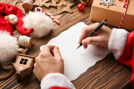 Santa Claus writing letter on wooden table Stock Photo