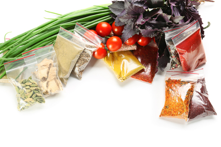 Composition with different spices in plastic bags on white background 免版税图像