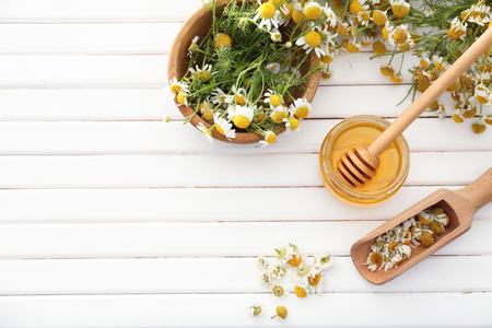 Jar of honey with chamomile flowers on wooden table