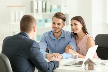 Agente inmobiliario que trabaja con clientes en la oficina