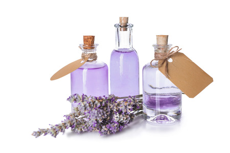 Bottles of essential oil with lavender on white background