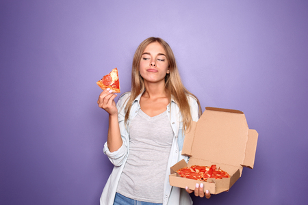 Young woman with delicious pizza on color background Imagens
