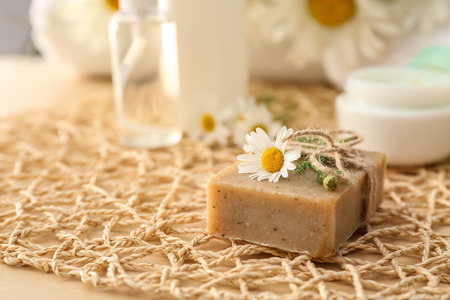 Bar of natural soap with chamomile flower on table