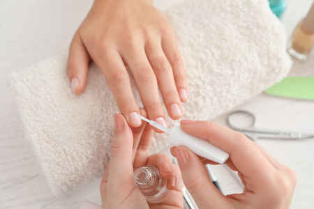 Young woman getting professional manicure in beauty salon, closeup