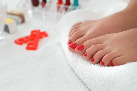 Young woman with stylish pedicure in beauty salon, closeup