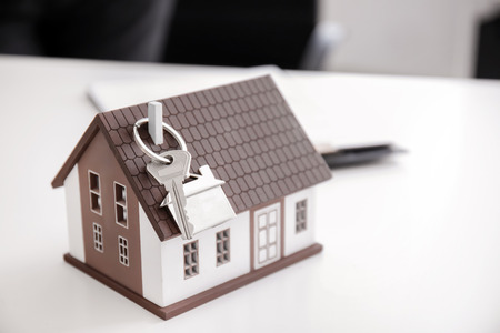 House model with key on table in office of real estate