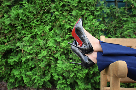 Young woman in stylish shoes resting on bench outdoors Stock Photo - 114751218