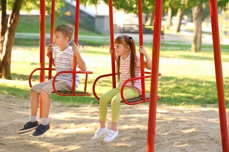 Cute little children swinging outdoors