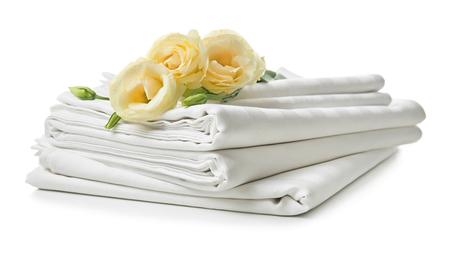 Pila de sábanas limpias sobre fondo blanco.