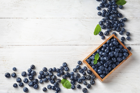 Crate with ripe blueberries on wooden table