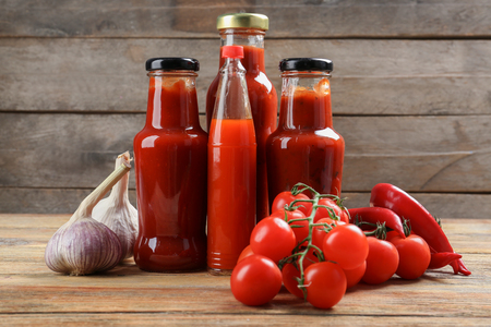 Bottles with tasty tomato sauces and on wooden table