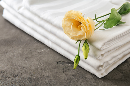 Stack of clean bed sheets and flower on grey background, closeup