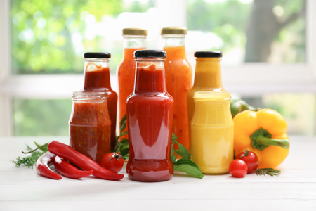 Glassware with different tasty sauces and vegetables on white table Foto de archivo