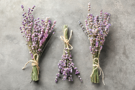 Bunches of beautiful blooming lavender flowers on grey background Imagens