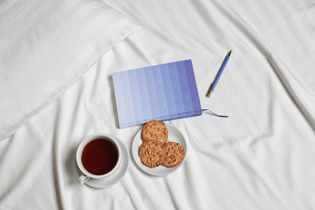 Cup of tea, cookies and notebook on bed linen