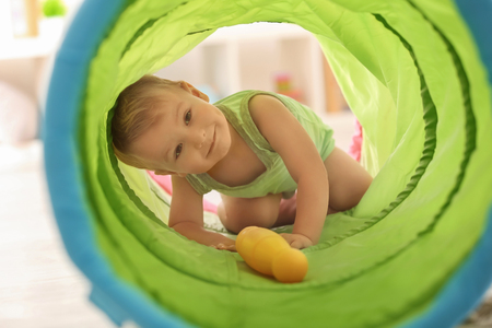 Cute little boy playing with toy tunnel at home