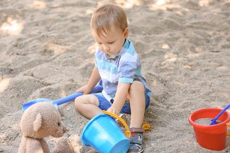 Cute little boy playing in sandbox outdoors