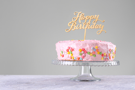 Stand with beautiful tasty birthday cake on table