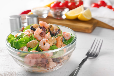 Bowl of delicious vegetable salad with seafood on table