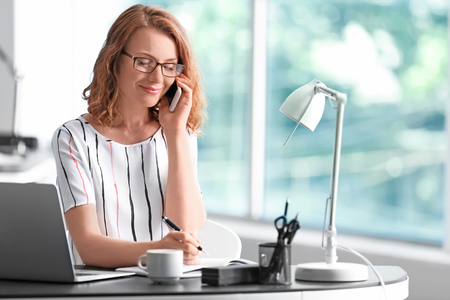 Successful businesswoman talking by mobile phone in office